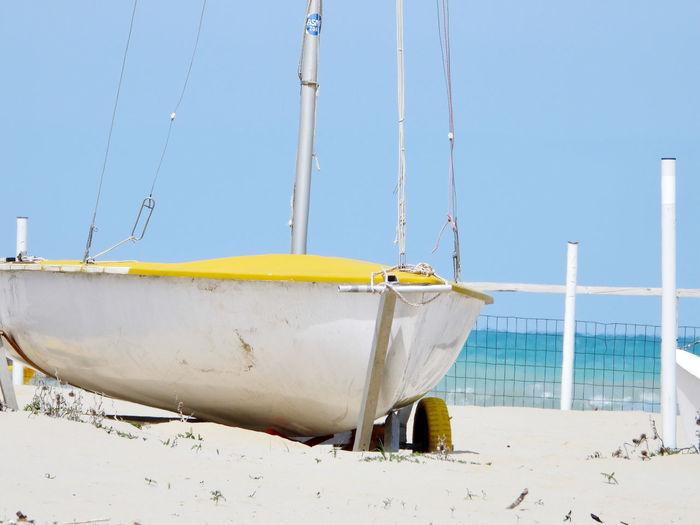 Sailboat moored on beach against clear blue sky
