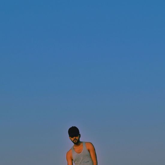 Low angle portrait of young man against clear sky at dusk