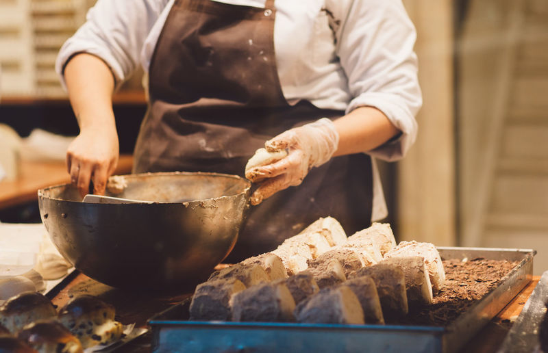 Midsection Of Female Chef Preparing Food On Table