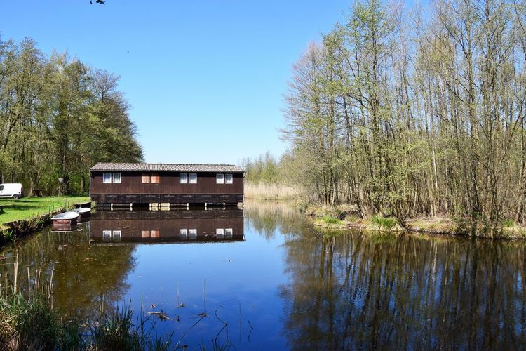 Am Ende des Areals findet sich ein Anglerdomizil. Water Plant Lake Tree Reflection Nature No People Tranquility Day Sky Architecture Built Structure Tranquil Scene Waterfront Beauty In Nature Scenics - Nature Outdoors Non-urban Scene Wood - Material