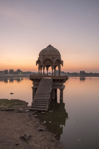 Gadi Sagar Lake during sunrise in Jaisalmer, India. Architecture Beauty In Nature Building Exterior Built Structure Clear Sky History Lake Nature No People Orange Color Outdoors Reflection Scenics - Nature Sky Sunset Tranquility Travel Travel Destinations Water Waterfront