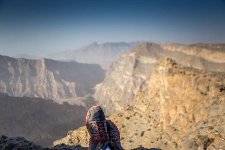 Low section of man wearing shoes on mountain against sky