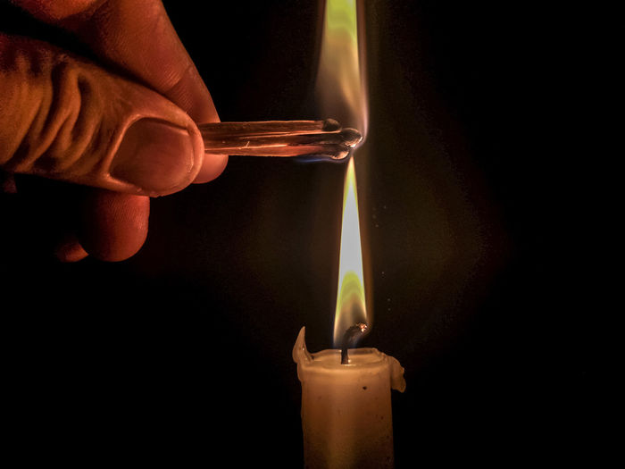 Close-up of hand burning candle against black background