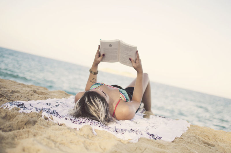 Sea Water Real People Beach One Person Sky Leisure Activity Lifestyles Land Horizon Sand Horizon Over Water Nature Relaxation Young Adult Day Beauty In Nature Lying Down Hairstyle Book Relaxing Reading Summer Outdoors