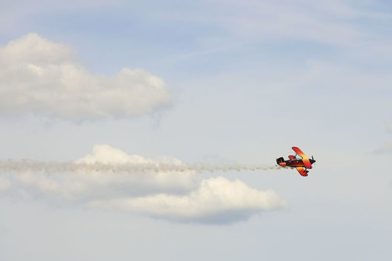 Low angle view of model toy airplane flying in sky