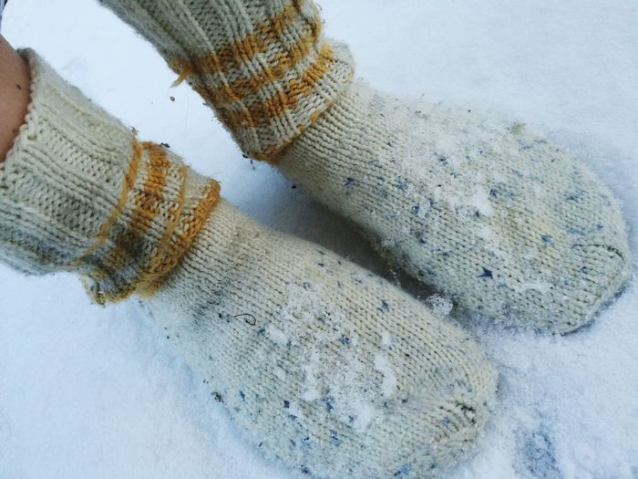 Low Section Of Person Wearing Wool Socks On Snow