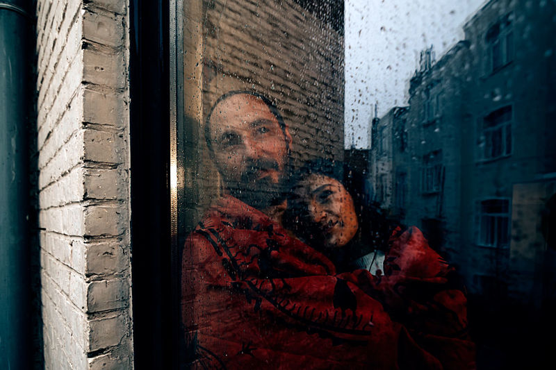 Couple wrapped in a red blanket looking outside from a backyard door window on a grey rainy day