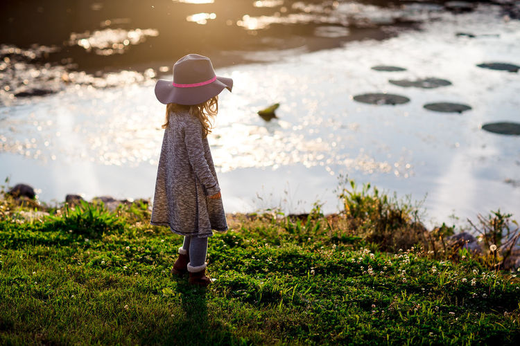 Beauty In Nature Child Childhood Children Only Day Grass Hat Nature Outdoors Standing Tranquility Water
