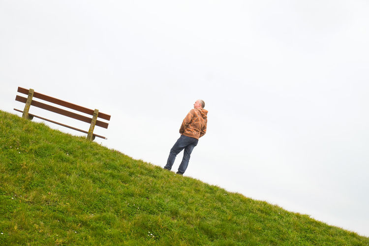 A single person standing next to a single empty wooden bench on the horizon above a grass field against a large grey clouded sky depicting loneliness, thinking, pondering, grieve, being alone, sadness One Person Full Length Plant Grass Nature Sky Adult Day Rear View Leisure Activity Green Color Walking Casual Clothing Standing Copy Space Men Land Field Landscape Outdoors