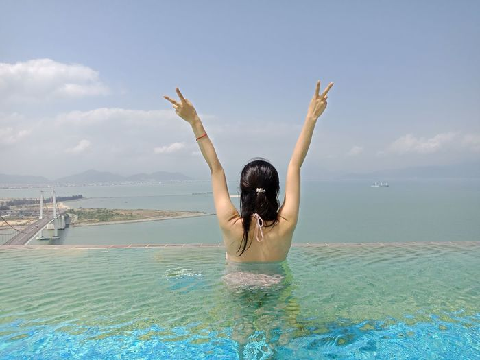 Rear view of young woman with arms raised in infinity pool against sky