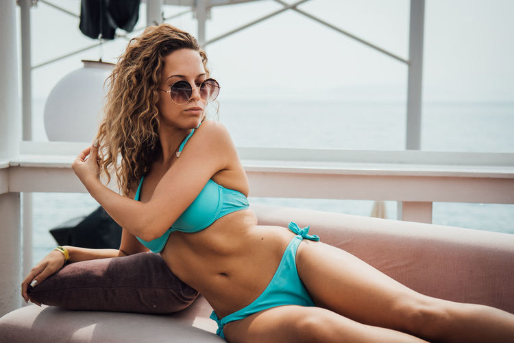 One Person Young Adult Young Women Leisure Activity Glasses Sitting Real People Relaxation Clothing Lifestyles Swimwear Adult Women Fashion Bikini Day Sunglasses Beauty Hairstyle Beautiful Woman Hair Outdoors