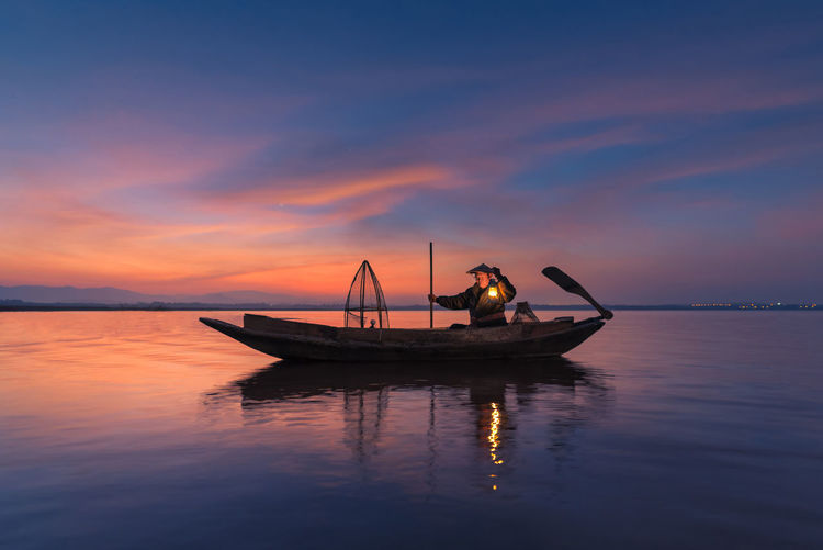 Fisherman in boat on lake against sky during sunset