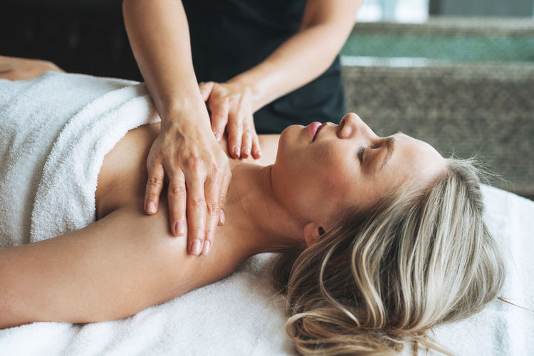 Attractive blonde young woman on couch with white linen enjoys hand facial massage in spa salon