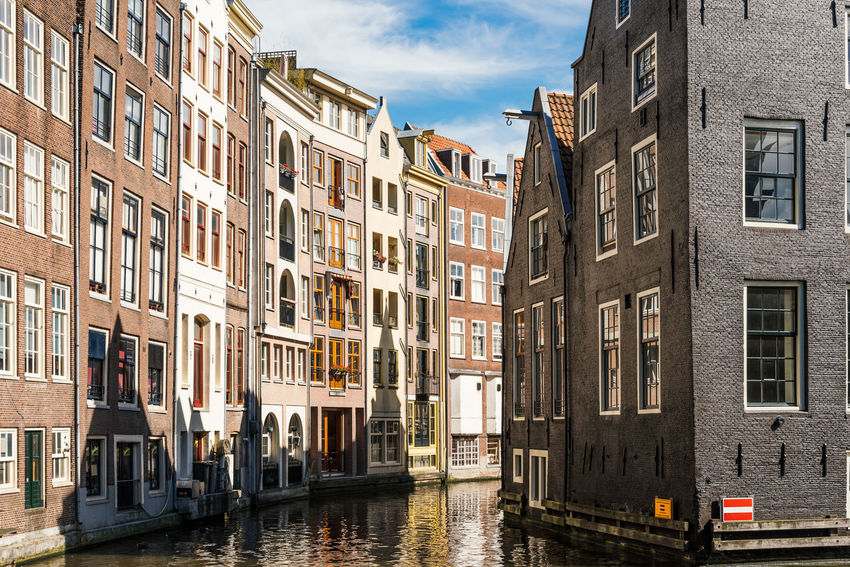 Amsterdam cityscape with canals in Red Light District Amsterdam Architecture Building Exterior Business Finance And Industry Canal City Cloud - Sky Cultures Day House Multi Colored No People Outdoors Red Light District Sky Travel Travel Destinations Water