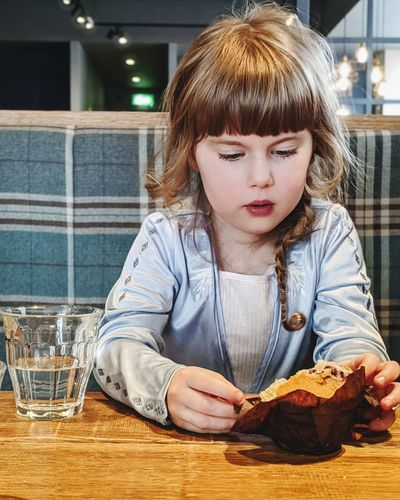 Portrait of girl with muffin on table
