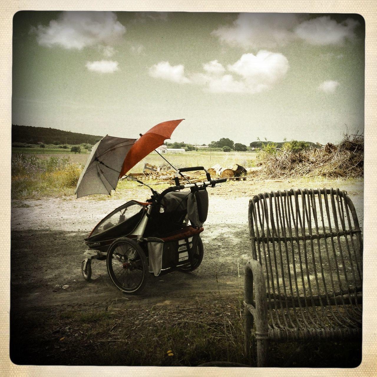 Wheelchair With Umbrella Against Sky
