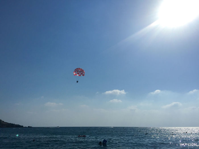 Low Angle View Of Parachute Over Sea Against Sky On Sunny Day