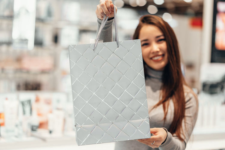 Portrait of smiling young woman shopping at cosmetic store