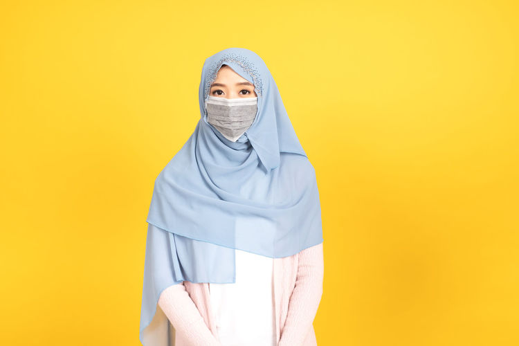 Portrait of mid adult woman against yellow background
