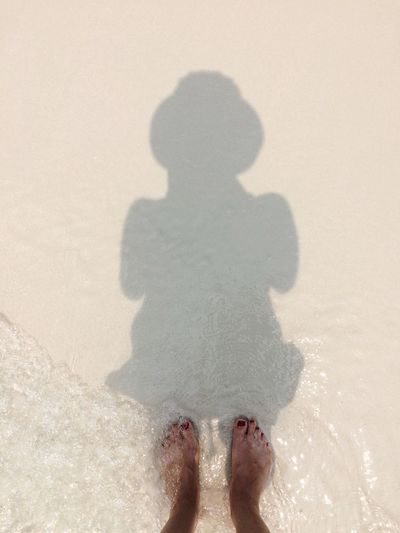 Shadow Of Woman Standing On Beach