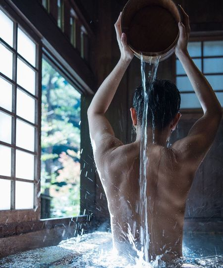 Rear view of shirtless man taking bath at home
