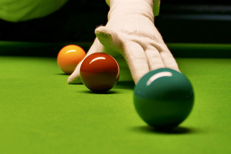 Cropped hand pointing at balls at pool table