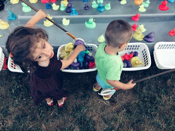 Siblings collecting toys in baskets against pond