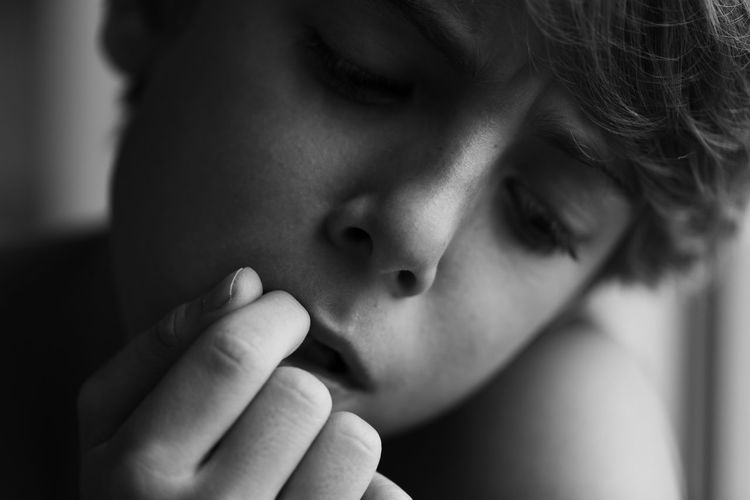 Close-up of boy with finger in mouth thinking