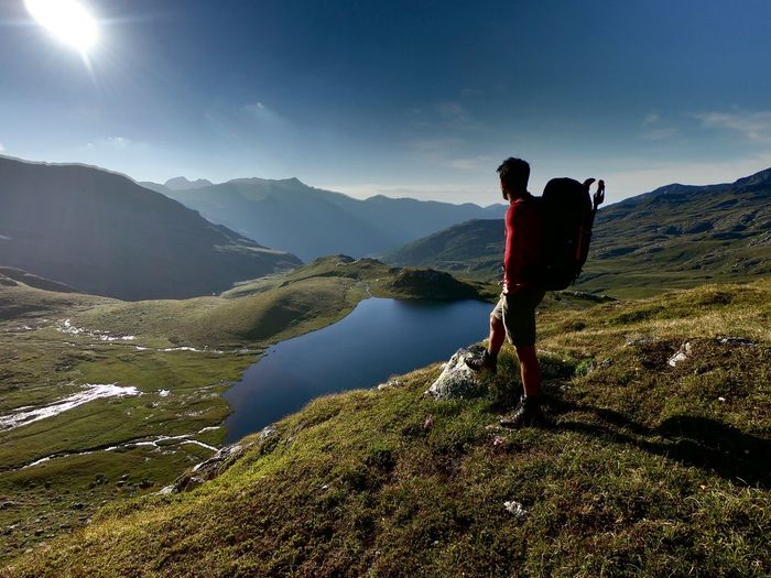 Side View Of Backpacker Standing On Mountain Against Sky