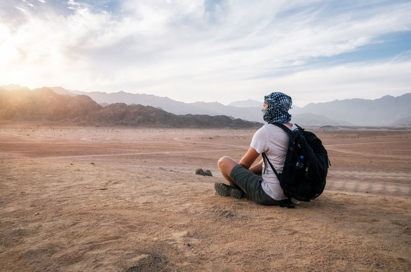Traveler wearing arabic head scarf with a backpack sits and looks at Sinai desert and mountains at sunset, Egypt Egypt Arid Climate Beauty In Nature Cloud - Sky Desert Landscape Land Landscape Leisure Activity Lifestyles Looking At View Mountain One Person Outdoors Real People Rear View Scenics - Nature Sinai Sitting Sky Sunset Tranquility Be Brave