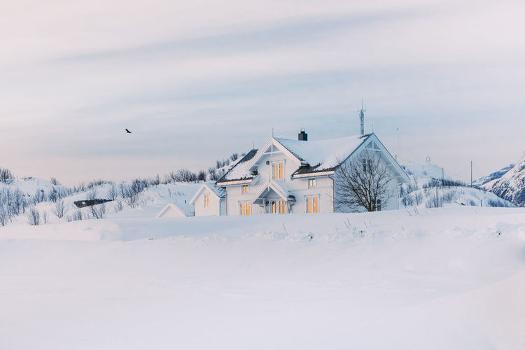House on snow covered field by building against sky