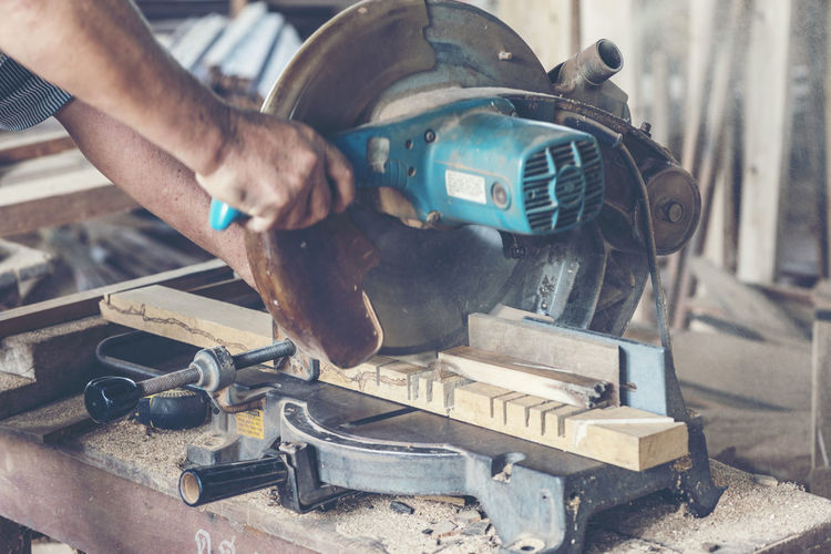Cropped hands of worker cutting wood on electric saw in workshop