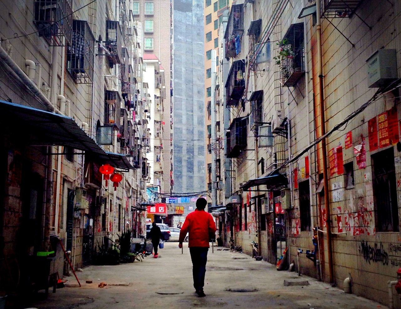Full length rear view of man walking on footpath amidst buildings in city