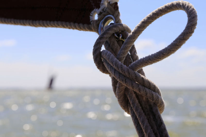 Close-up of rope tied on metal against sky