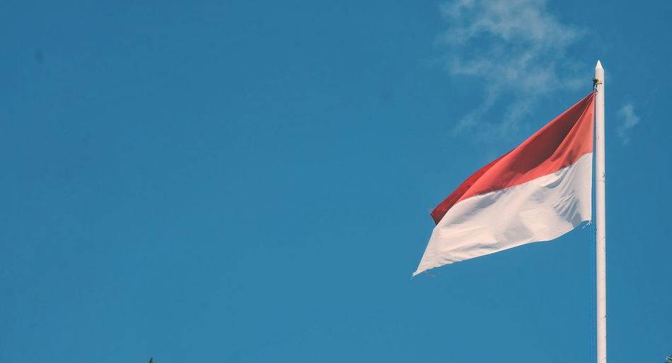 Low angle view of indonesian flag waving against blue sky