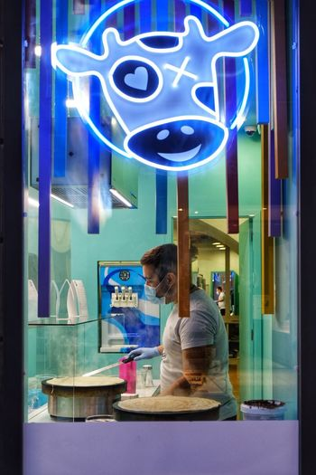Woman standing by glass window at store
