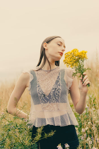 Beautiful young woman standing by flower on field