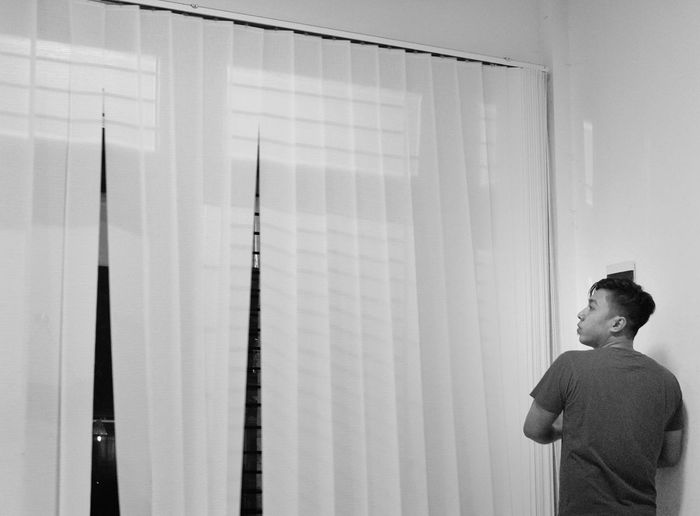Side view of boy standing against curtain
