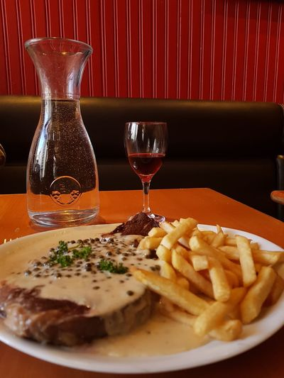 It was sooooo good! Glass Jar Plate Red Beef Beefsteak EyEmNewHere Team France 🇫🇷 Entrecote French Fries Sauce Poivre Pepper French French Food Restaurant Wineglass Drink Alcohol Wine Drinking Glass Close-up Food And Drink Steak Red Meat Served