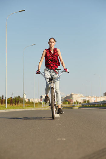 Young woman cyclist in red blouse moves on bicycle on road smiling