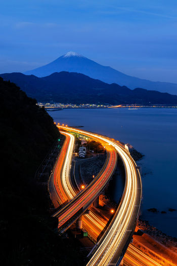 Aerial view of Mountain Fuji with express way, roads at night in Shizuoka. Fuji five lakes, Japan. Landscape with hills. Mountain Fuji Fujisan Japan Fujikawaguchiko Landscape Nature Expressway Mountain Transportation Illuminated Road Light Trail High Angle View Mountain Range Long Exposure Sky Motion Speed No People Night Blurred Motion Water Scenics - Nature City Beauty In Nature Dusk Outdoors Multiple Lane Highway