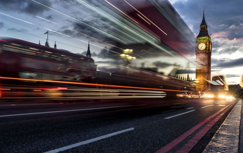 Light trails by big ben in city street amidst buildings