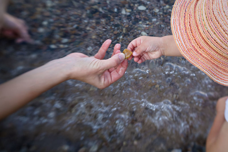 High angle view of woman hand and schild hand on rock