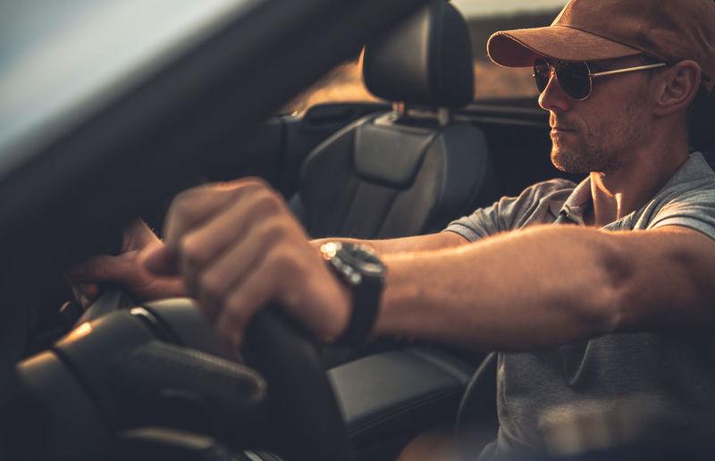 Mature man wearing sunglasses sitting in car