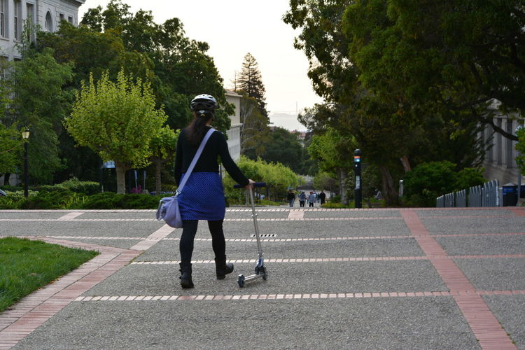 Rear View Of Woman With Push Scooter On Footpath