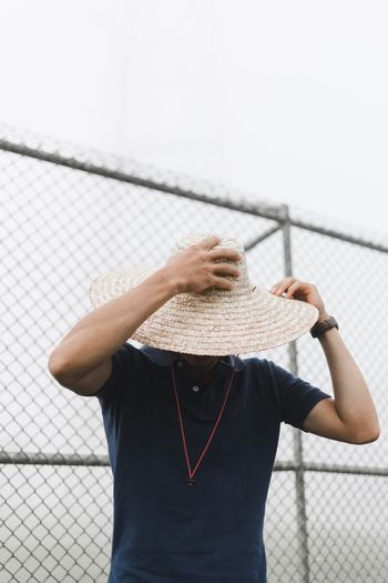Man wearing hat against chainlink fence