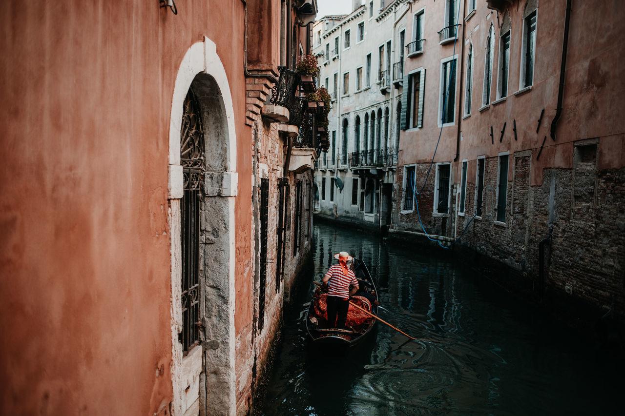 Rear view of man in boat against buildings