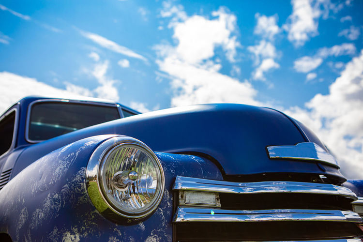 Close-up of vintage car against blue sky
