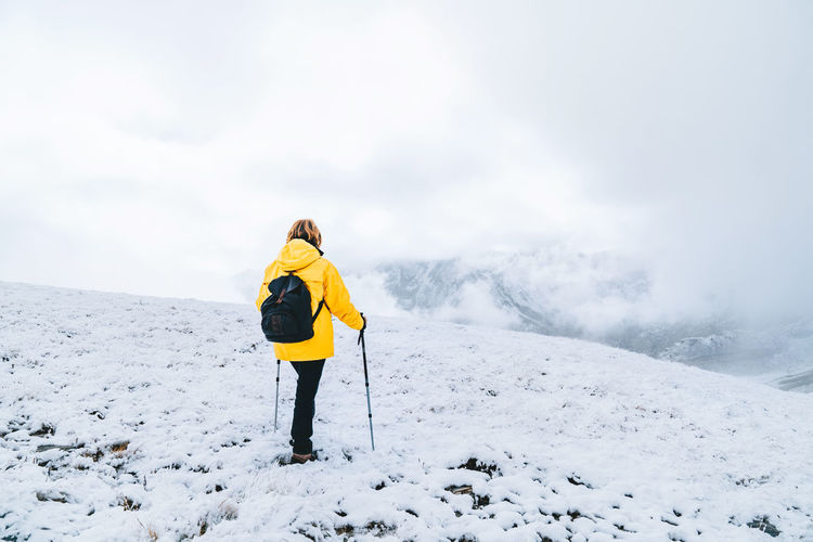 Woman on snowcapped mountain against sky