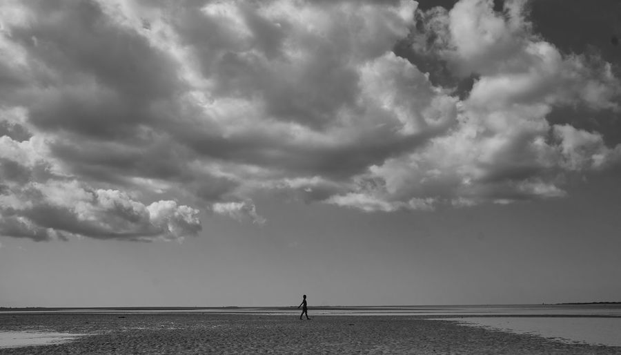 Scenic view of sea with person walking at beach against sky